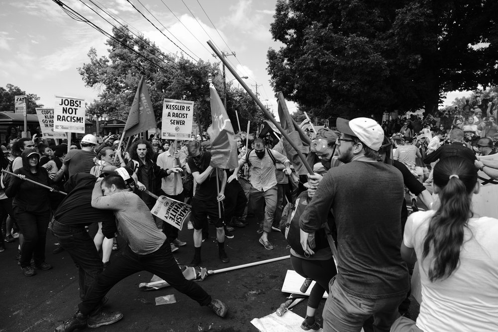 Numerous skirmishes broke out in the streets where protesters chanted and attempted to deny white supremacists access to Emancipation Park. Street medics played a pivotal role in mitigating injuries, helping those injured by tear gas and pepper spray, running into the street to cover gas grenades with buckets, and providing water and snacks to those who needed them.