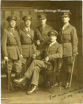 "Credit: Photo courtesy of the  Musée Héritage Museum  CA MHM 2014.22.02  Title: This photograph depicts Brigadier-General Raymond Brutinel in military uniform seated with four members of his Machine Gun Brigade standing behind him. From left to right: Captain J.K. Lawson, Major J.D. Foster, Captain M.R. Lever (Marshall), and Lieutenant P.M. Hume. An inscription on the photograph reads ""G.O.C. Canadian Machine Gun and Staff--11th Nov""  Date: ca 1919  Photographer/Illustrator: N/A"