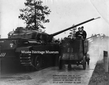 "Credit: Photo courtesy of the  Musée Héritage Museum  CA MHM 2014.22.06  Title: This photograph depicts the armoured vehicle designed by Brigadier-General Raymond Brutinel in 1914 driving alongside a 1956 tank. General F..F.. Worthington is driving the armoured vehicle. A caption reads ""Quarante-deux ans se sont ecoules entre le char blinde Canadien de Brutinel de 1914 et le char d'assaut de 1956"" [Forty-two years have elapsed between the Canadian armoured tank of Brutinel of 1914 and the tank of 1956.]   Date: 1956  Photographer/Illustrator: N/A"