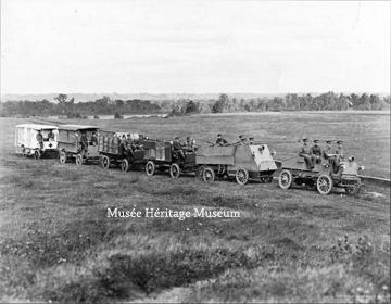 Credit: Photo courtesy of the  Musée Héritage Museum  CA MHM 2014.22.07  Title: This photograph depicts six vehicles from the 1st Automobile Machine Gun Brigade commanded by Brigadier-General Raymond Brutinel driving in single-file across a field. The first vehicle is carrying four military men, the second is the armoured vehicle, followed by three transport vehicles and a field ambulance.   Date: ca 1914-1915  Photographer/Illustrator: Surveyor General's Office in Ottawa.     This photo is one of many taken during an inspection of the unit by the Governor-General, the Duke of Connaught, at the Rockcliffe Rifle Range in Ottawa, September 1914, just before entraining for Montreal and embarking for England.
