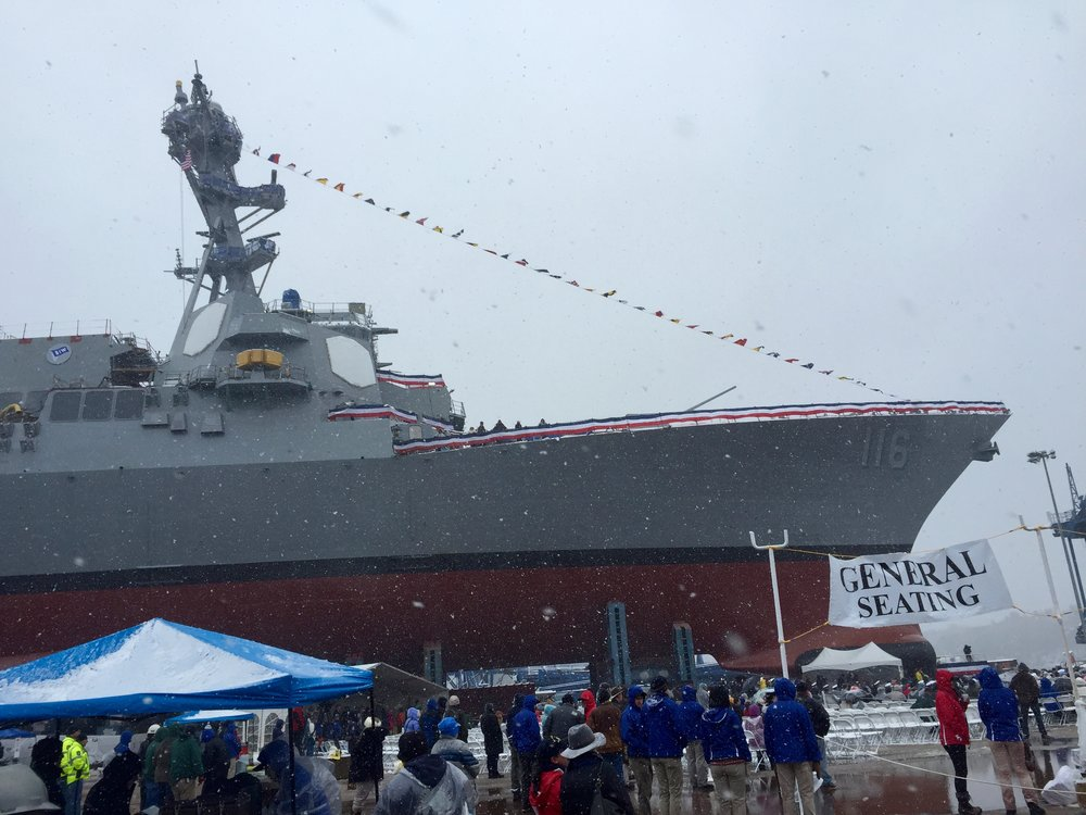 Snow swirls around the future USS Thomas Hudner at its christening at the Bath Iron Works shipyard in Bath, Maine. Photo by Rick Holmes