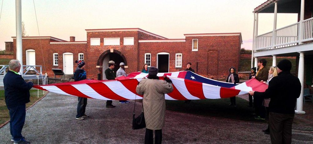 Visitors to Fort McHenry in Baltimore help a ranger retire the Star-Spangled Banner at sunset.