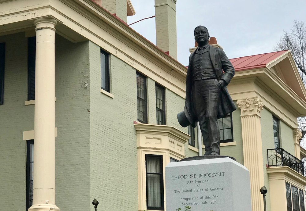 A statue of Theodore Roosevelt stands by the house where he was sworn in as president.