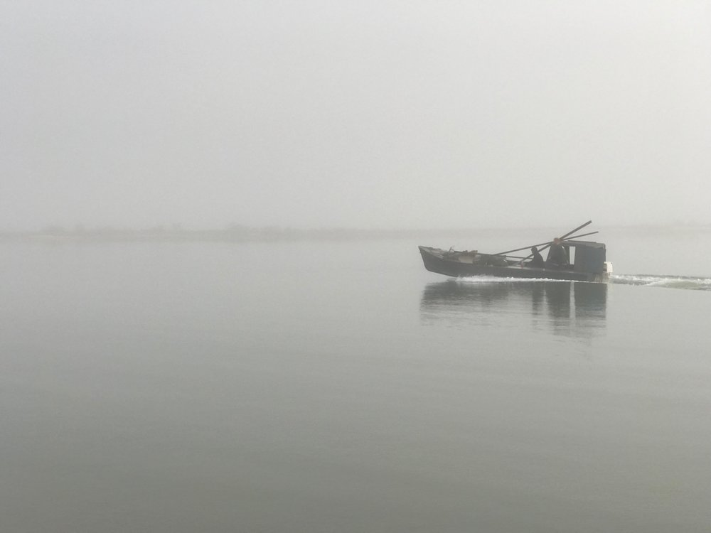 An oyster boat returns to foggy Eastpoint, Fla., after a long day