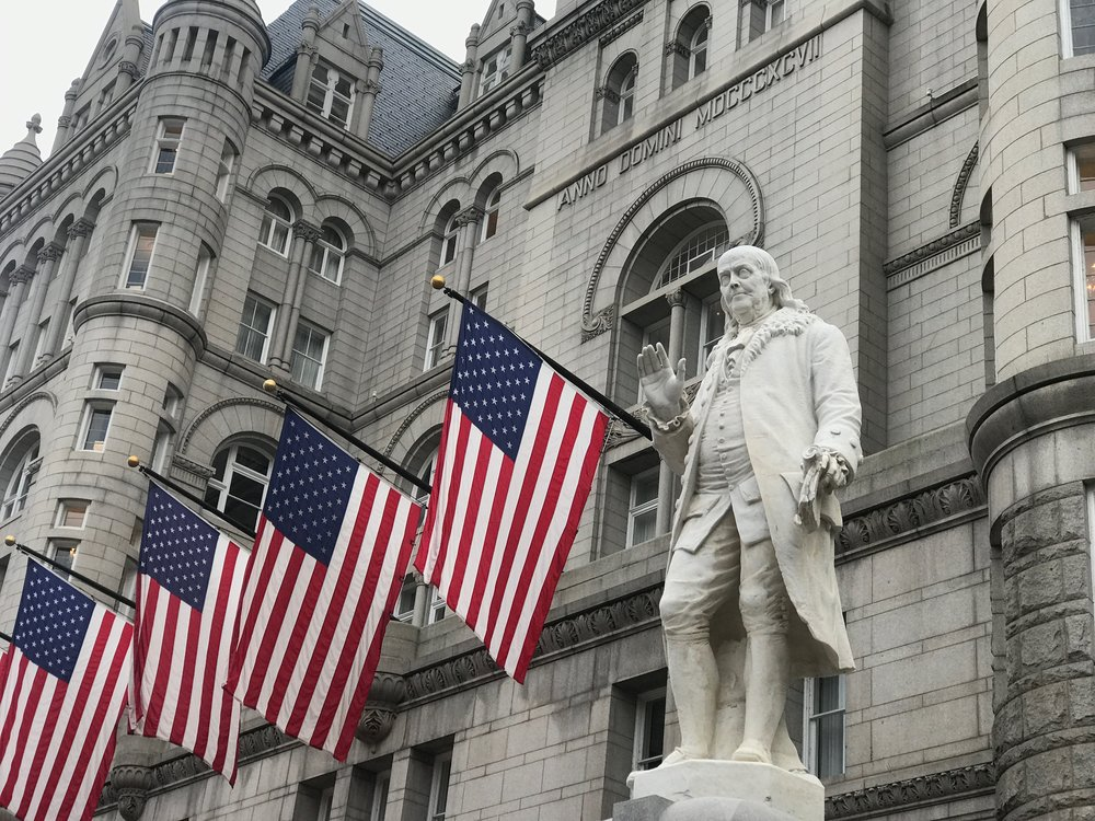 A statue of Benjamin Franklin, who served as the nation's first postmaster general, stands outside the former Post Office Building in Washington, which is now home of the Trump International Hotel.