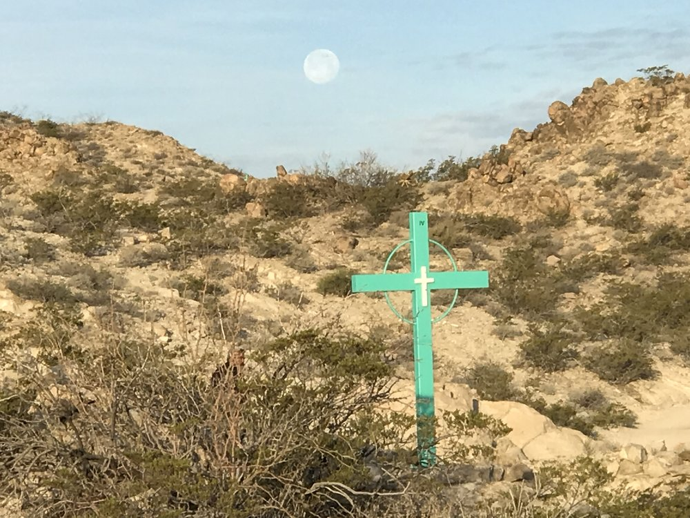 A full moon sets behind a cross marking the path up Christo Rey Mountain just outside El Paso.