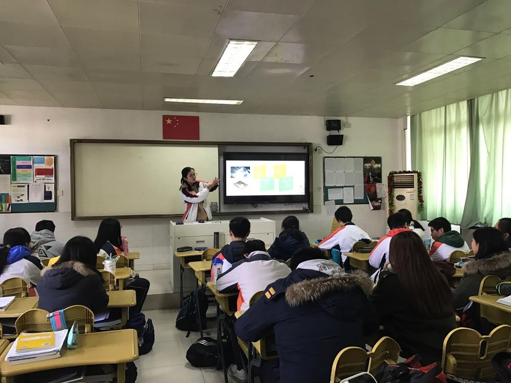 members giving a speech at a Chinese high school on female period products.