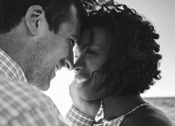 man embraces wife in his arm, foreheads touching, black and white