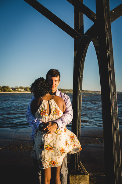 couple hugging on pier as light wraps around them and wind moves her dress
