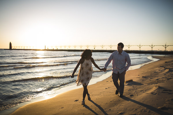 couple running along beach and in hand, golden light
