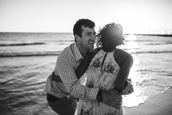 playful embrace of couple on beach, black and white