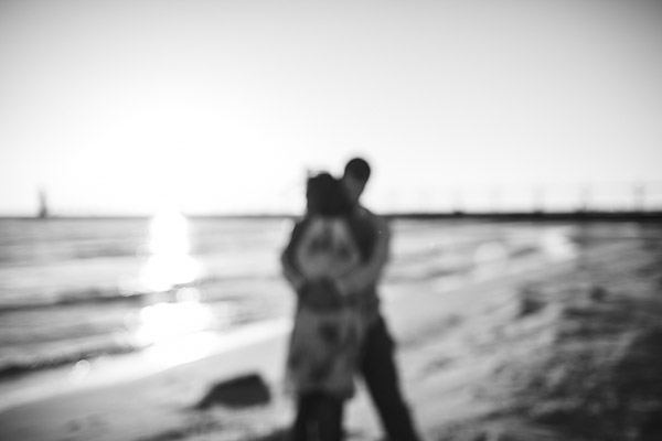 couple embracing on beach, out of focus, black and white, moody, intimate