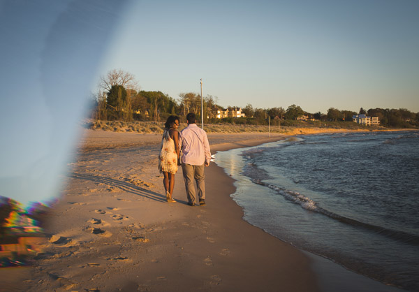 couple walking along beach as wife looks back, prism, golden hour
