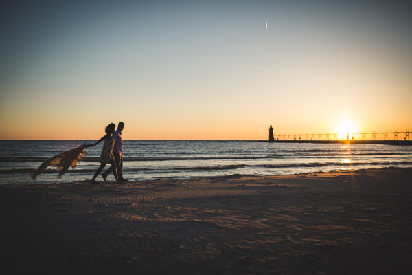 couple walking along beach in golden light, scarf flowing behind, movement, connection
