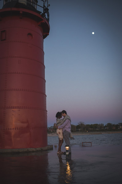 couple hugging in front of lighthouse with moon in background