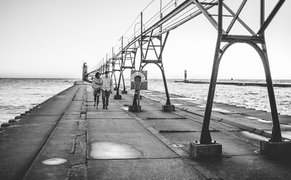 couple walking along pier, hand in hand, connection, movement, black and white