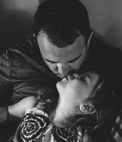 father kissing his daughter, black and white