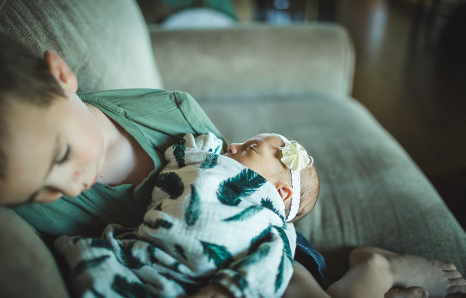 tender moments of brother resting with newborn baby sister on couch