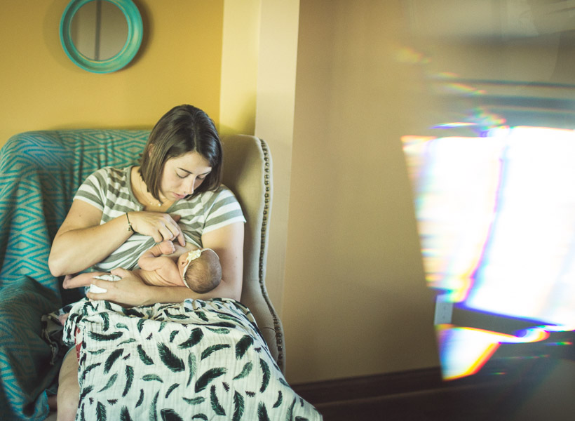 mother nursing her newborn child in soft window light of prism