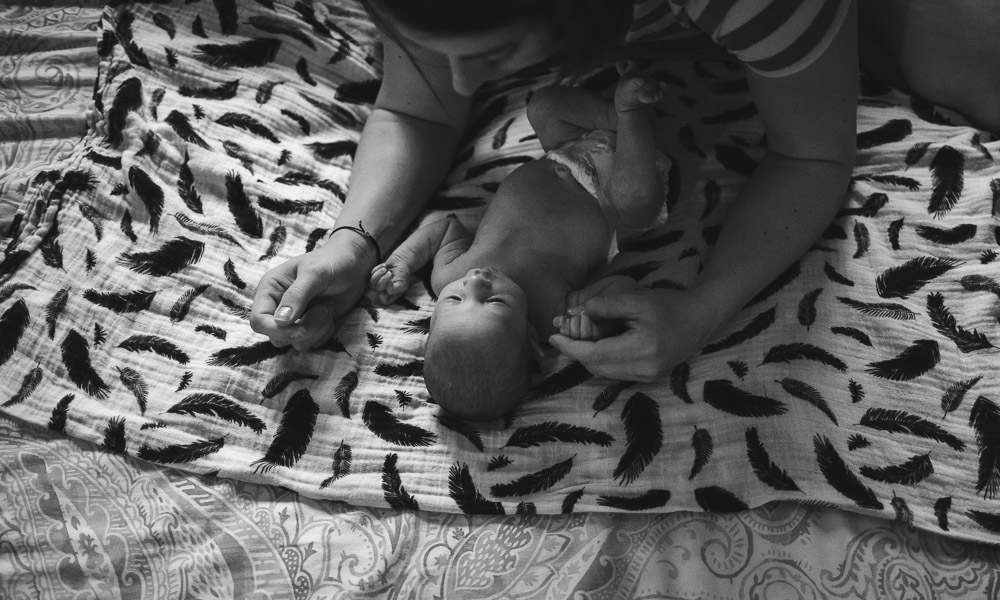mother admiring her newborn child on bed; black and white