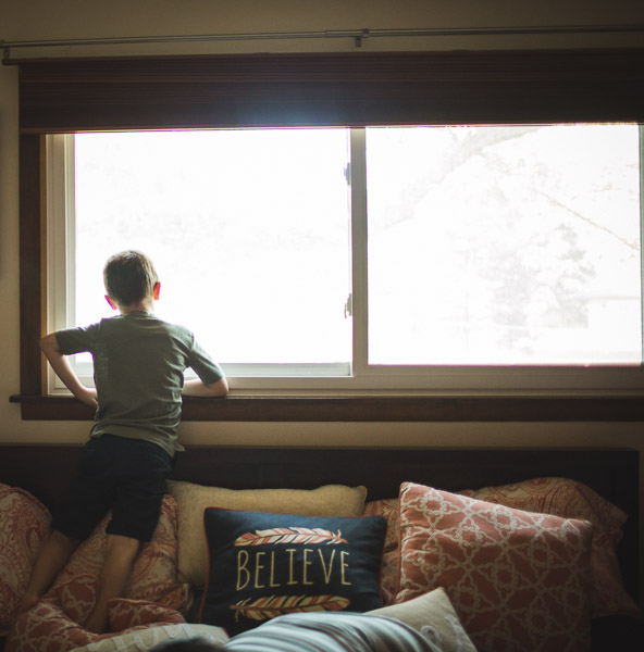 boy peeking outside of large window, reflecting