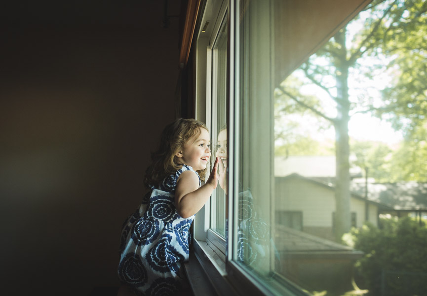 little girl looking out window with face pressed against the glass, wonder