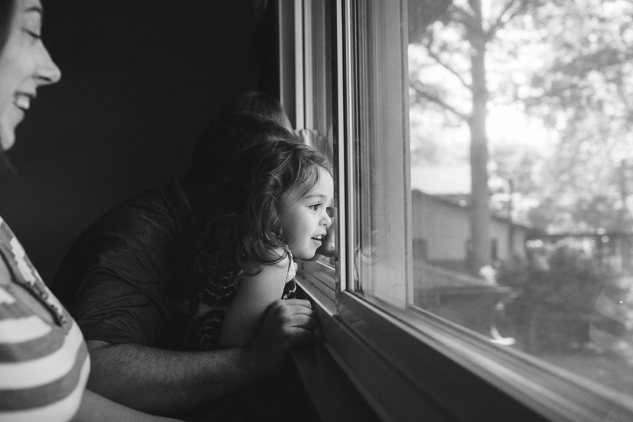 little girl looking out window with mother; black and white