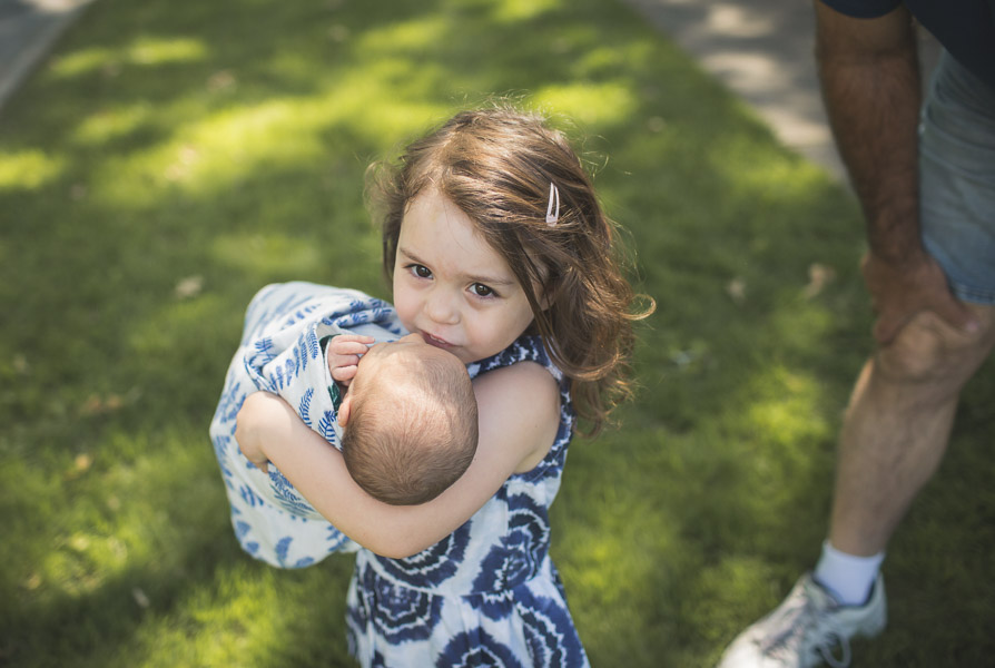 sister carrying newborn baby across yard, movement, powerful, connection