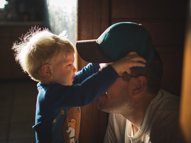 father and son connecting through loving play with hat