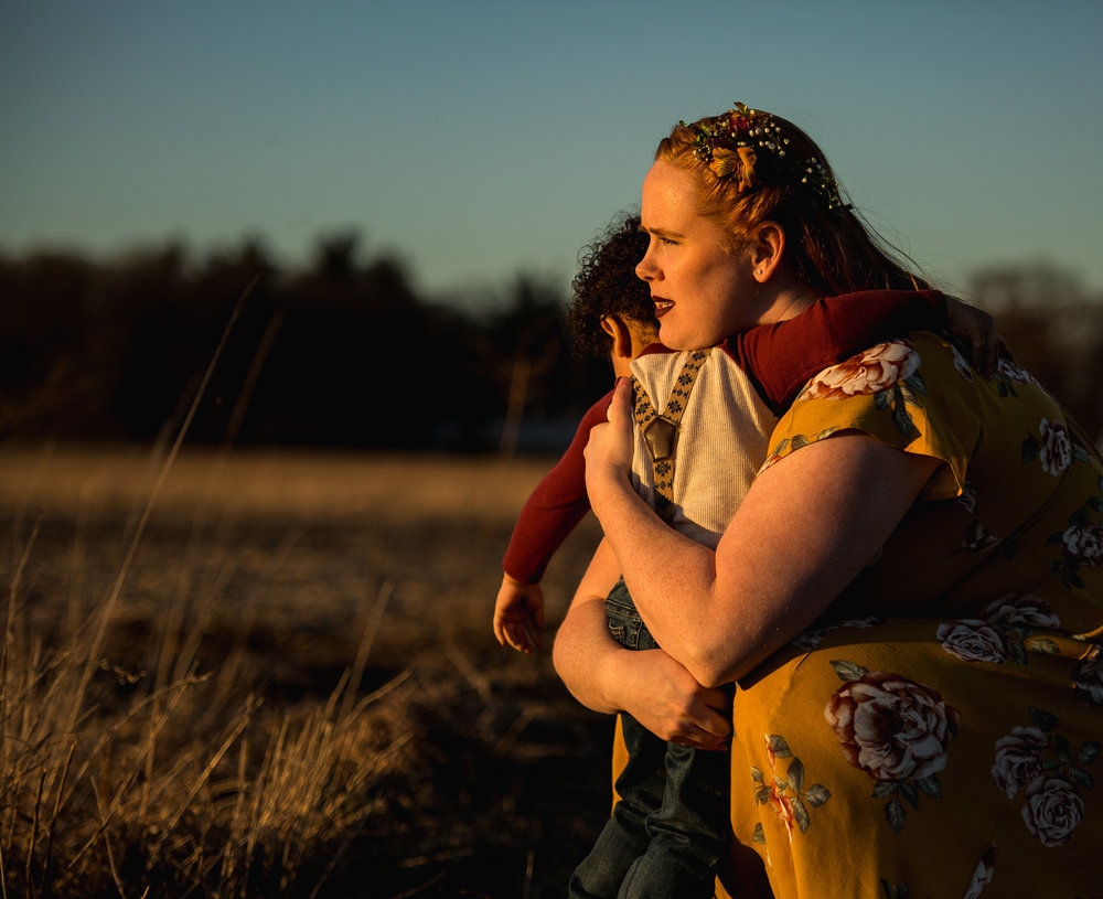Mothering lovingly hugging her son in wide open field during golden sunset