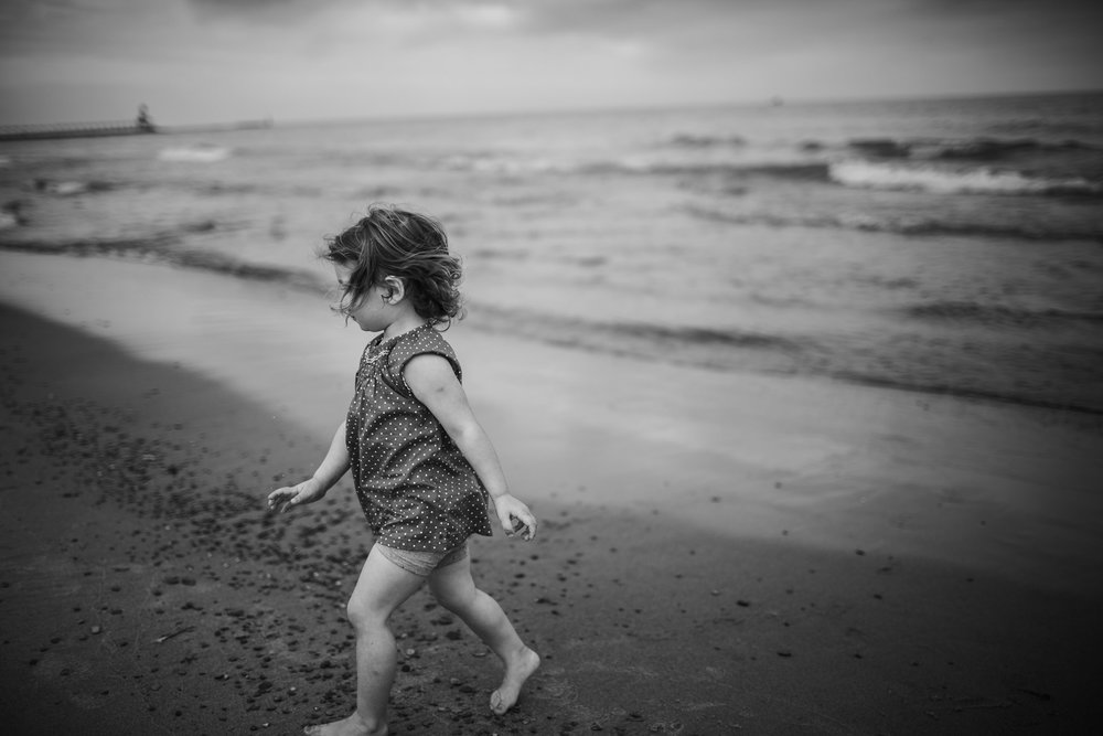 Girl exploring by the ocean as the wind sweeps through her hair, Lake Michigan
