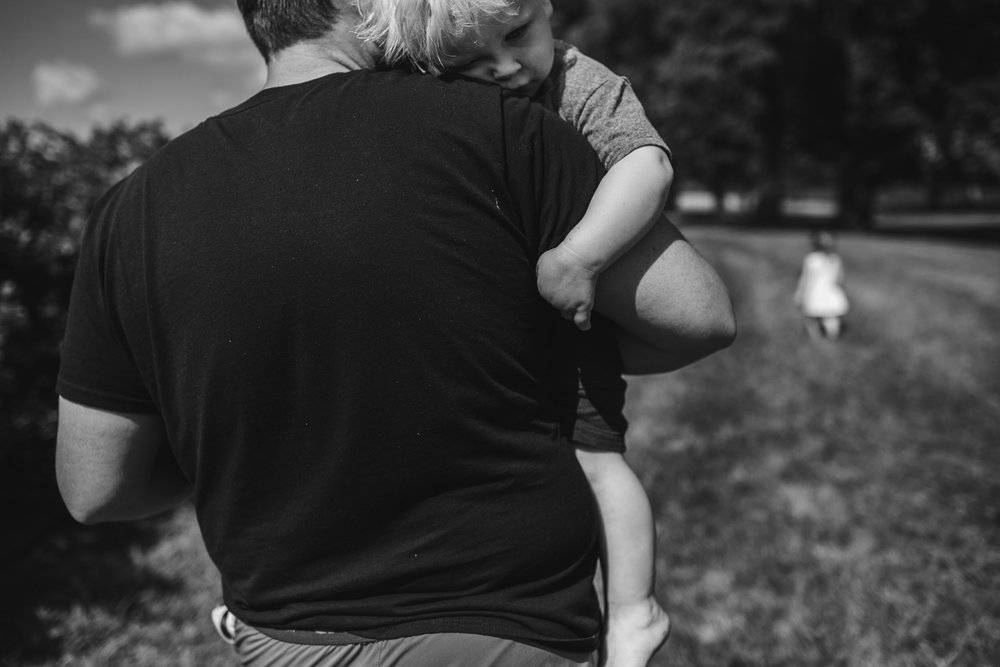 close up image of boy resting on fathers shoulder, cuddled close in his arms, connected and cared for