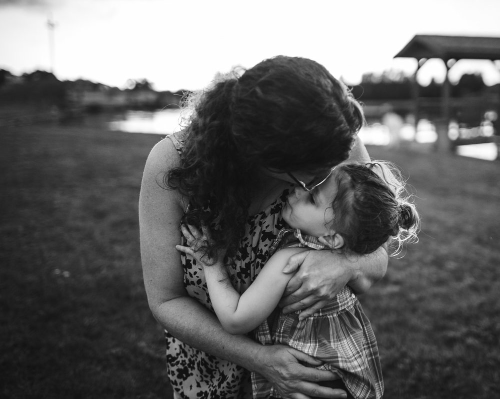 grandmother embracing child, warm connection, loving, powerful black and white in field by pond