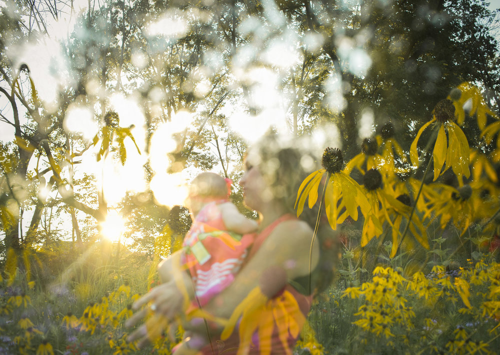 Multiple Exposure image of mother cradling daughter within daisy field and golden sunlight