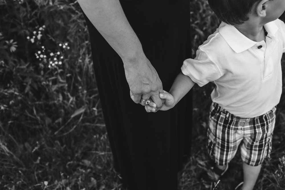 Detail portrait of mother and son holding hands, black and white, connection, emotional storytelling
