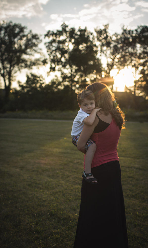 mother walking with son cradled on her arm as he glances at the camera, golden evening backlight in wide open field
