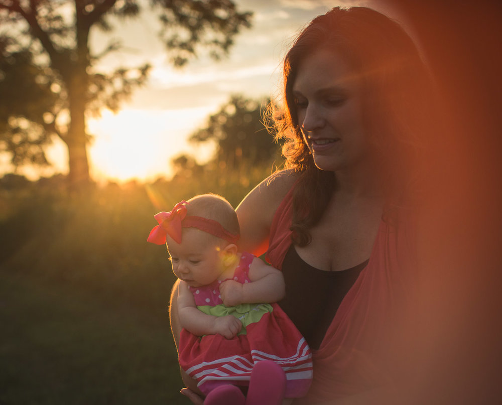 Mother holding child in warm sunlight with lens flare, backlight