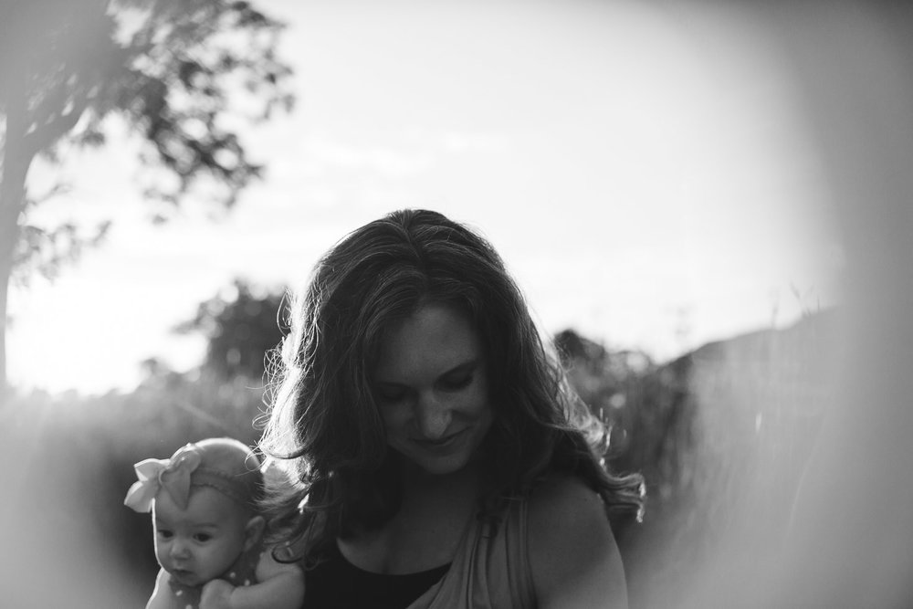 Mother embracing her child in love, as she looks down in gratitude, backlight, lens flare, bokeh, black and white, emotional motherhood portrait