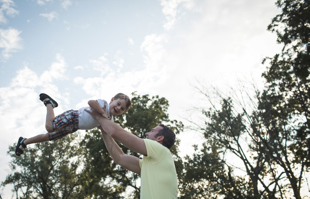 Father tossing son into air in playful fun