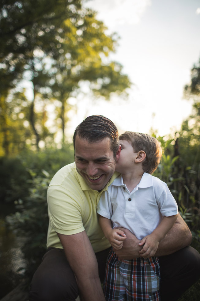 Son kissing father on the cheek surrounded by trees and golden light