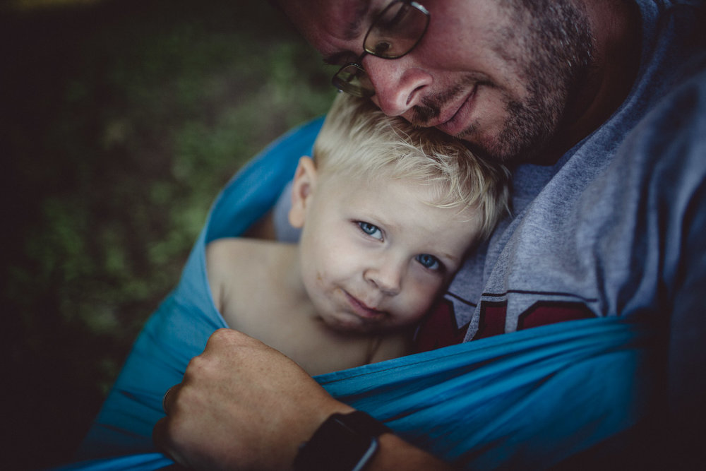 Portrait of son resting in fathers arms, shadow light, natural light