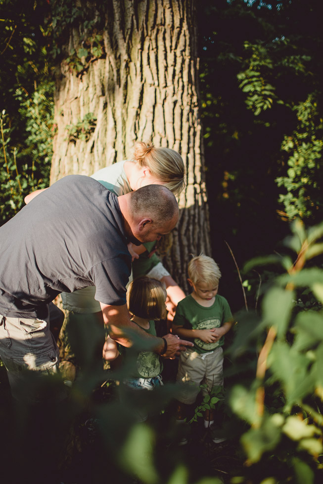Loving family exploring under trees, Shadow light play