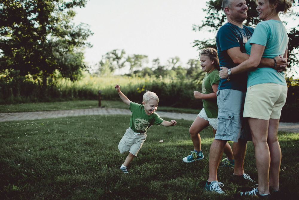 children playfully running around parents in open field at sunset