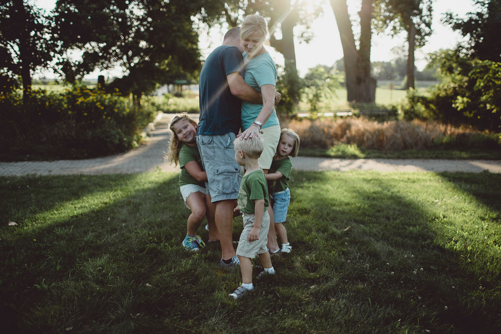 mother placing hand on sons head while children playfully run around parents in open field at sunset