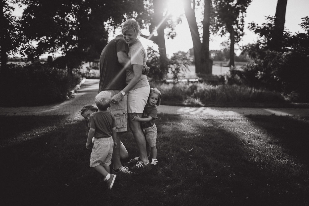 sun flare, family bonding and play in open field, black and white