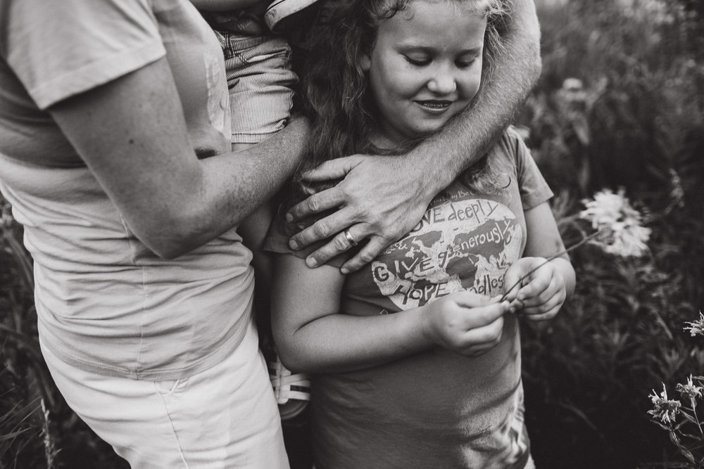 Father's hand across daughters shoulders in loving embrace, connection