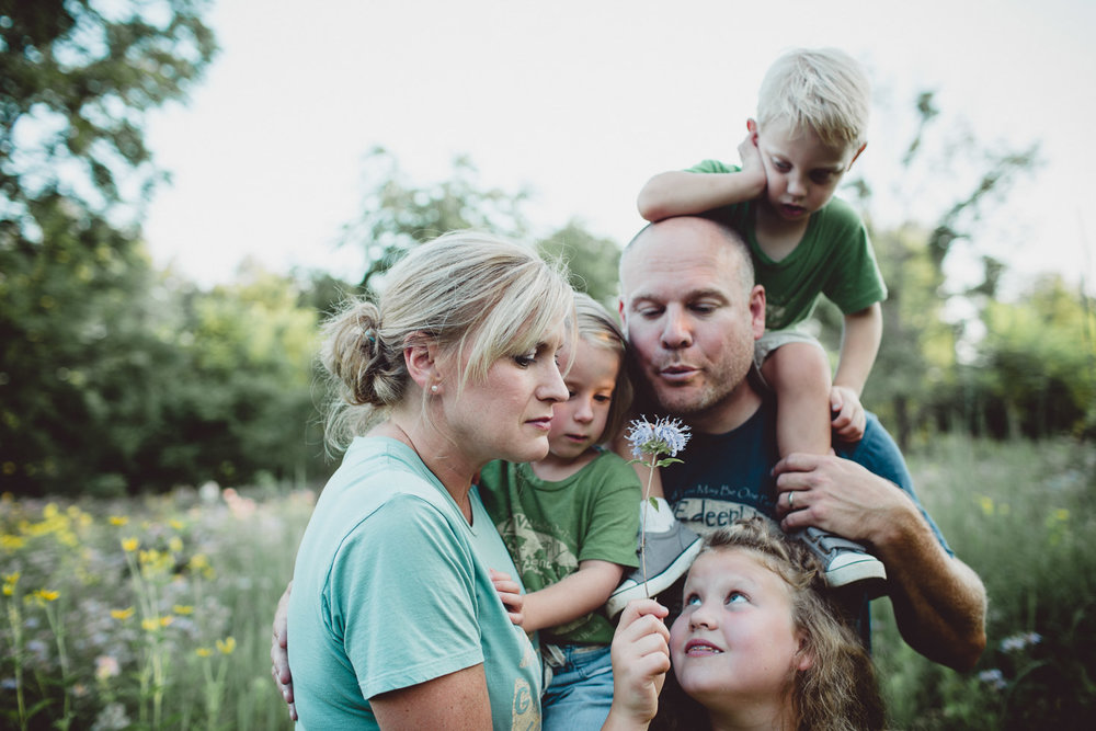 father blowing dandelion with family