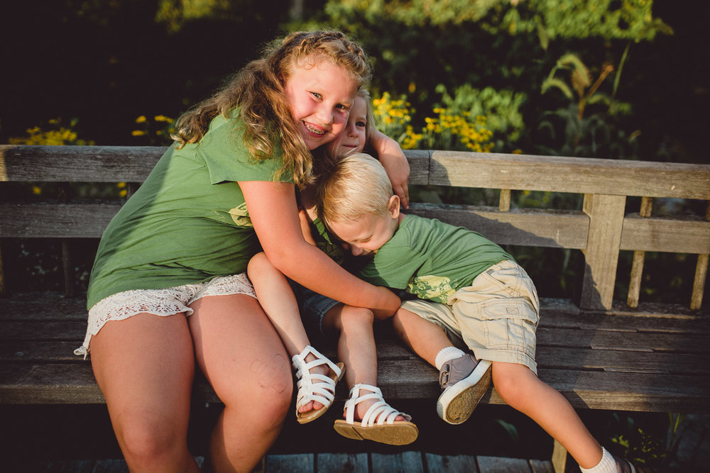 siblings hugging on bench in harsh sunlight