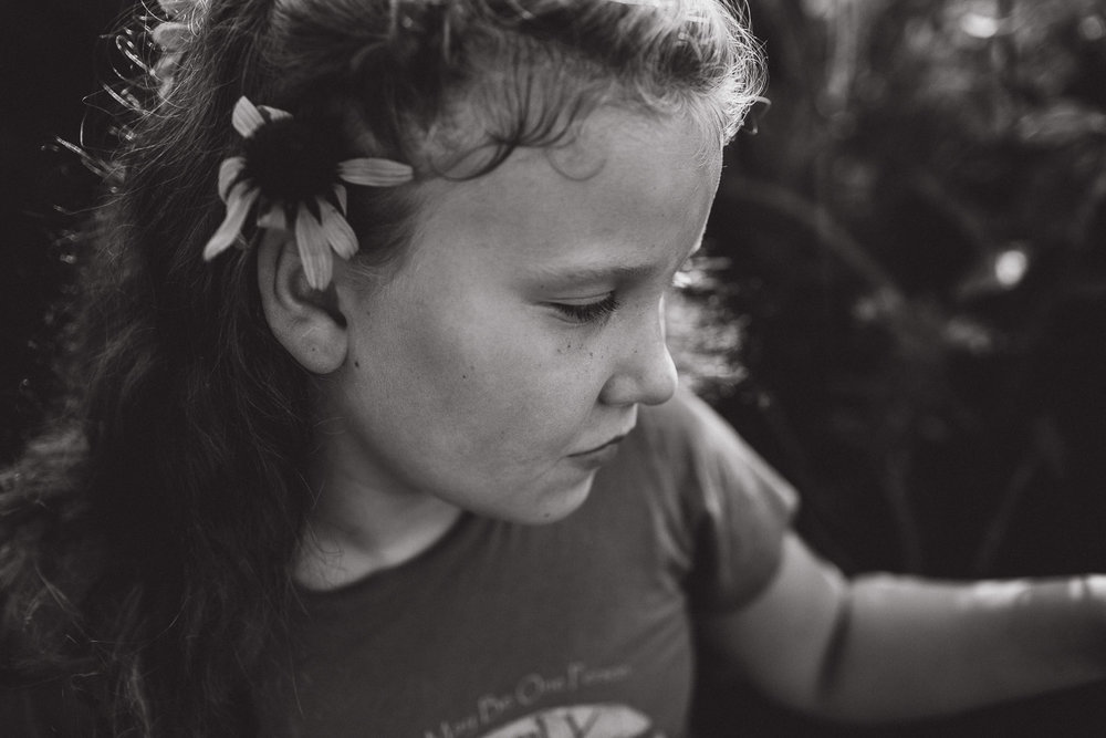 close-up side portrait of daughter admiring the flowers, black and white image