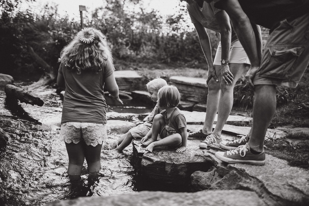 family playing in creek, black and white
